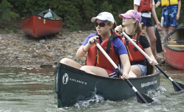 Two girls paddling a canoe