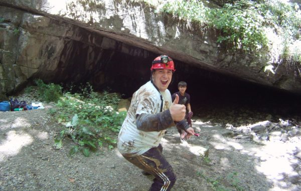 A muddy caver gives the camera a thumbs-up.